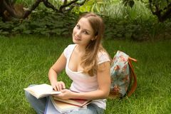 Estudiante universitario de la mujer con el libro studing en parque Imágenes de archivo libres de regalías