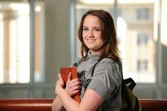 Estudiante universitario de la mujer joven que sostiene un libro Foto de archivo libre de regalías