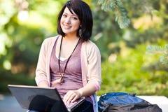 Estudiante universitario de la raza mezclada con la computadora portátil fotos de archivo