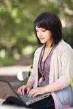 Estudiante universitario de la raza mezclada con la computadora portátil Imagen de archivo