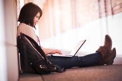 Estudiante universitario de la raza mezclada con la computadora portátil Imagenes de archivo