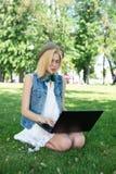 Estudiante universitario de la raza mixta que se sienta en el funcionamiento de la hierba Imagenes de archivo