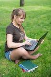 Estudiante universitario de la raza mixta que se sienta en el funcionamiento de la hierba Imágenes de archivo libres de regalías