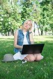 Estudiante universitario de la raza mixta que se sienta en el funcionamiento de la hierba Fotos de archivo