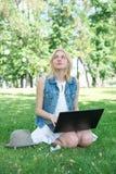 Estudiante universitario de la raza mixta que se sienta en el funcionamiento de la hierba Fotografía de archivo
