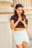 Estudiante universitario de sexo femenino americano joven que manda un SMS en salidas del teléfono celular Fotografía de archivo libre de regalías