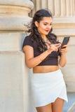 Estudiante universitario de sexo femenino americano joven que manda un SMS en salidas del teléfono celular Fotos de archivo libres de regalías