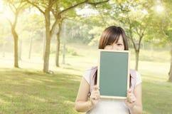 Estudiante universitario de sexo femenino asiático que muestra la pizarra en blanco Fotografía de archivo