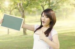 Estudiante universitario de sexo femenino asiático que señala en la pizarra en blanco Imagen de archivo libre de regalías