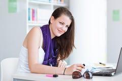 Estudiante universitario de sexo femenino bonito en la biblioteca Imágenes de archivo libres de regalías