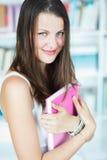 Estudiante universitario de sexo femenino bonito en la biblioteca Imagen de archivo libre de regalías
