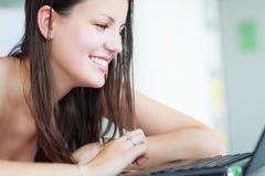 Estudiante universitario de sexo femenino bonito en la biblioteca Imagen de archivo
