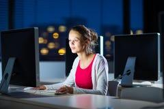 Estudiante universitario de sexo femenino bonito, joven que usa un equipo de escritorio Imagen de archivo