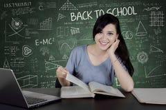 Estudiante universitario de sexo femenino con el libro en la sala de clase Imágenes de archivo libres de regalías