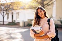 Estudiante universitario de sexo femenino con los libros al aire libre Imagen de archivo libre de regalías