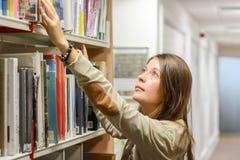 Estudiante universitario de sexo femenino en la biblioteca Fotos de archivo