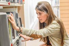 Estudiante universitario de sexo femenino en la biblioteca Fotos de archivo libres de regalías
