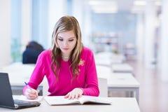 Estudiante universitario de sexo femenino en una biblioteca Imagenes de archivo