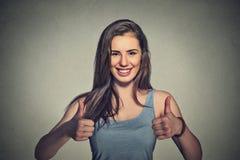 Estudiante universitario de sexo femenino feliz que muestra los pulgares para arriba Imagen de archivo libre de regalías