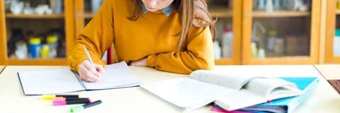 Estudiante universitario de sexo femenino joven en la clase de química, escribiendo notas Estudiante enfocado en sala de clase foto de archivo libre de regalías