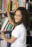 Estudiante universitario de sexo femenino que alcanza para un libro de la biblioteca Foto de archivo libre de regalías