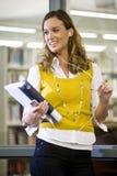 Estudiante universitario de sexo femenino que cuelga hacia fuera en biblioteca Fotos de archivo