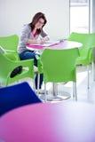 Estudiante universitario de sexo femenino que hace el campus del homeworkon Foto de archivo