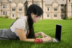 Estudiante universitario de sexo femenino que mecanografía en el ordenador portátil Foto de archivo