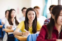 estudiante universitario de sexo femenino que se sienta con los compañeros de clase Imágenes de archivo libres de regalías