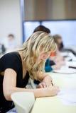 Estudiante universitario de sexo femenino que se sienta en una sala de clase Foto de archivo libre de regalías