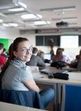 estudiante universitario de sexo femenino que se sienta en una sala de clase Fotos de archivo