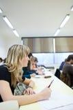 Estudiante universitario de sexo femenino que se sienta en una sala de clase Imagenes de archivo