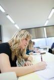 Estudiante universitario de sexo femenino que se sienta en una sala de clase Imágenes de archivo libres de regalías