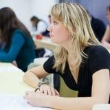 Estudiante universitario de sexo femenino que se sienta en una sala de clase Imagen de archivo libre de regalías
