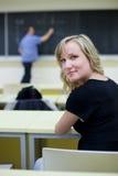 Estudiante universitario de sexo femenino que se sienta en una sala de clase Fotos de archivo libres de regalías