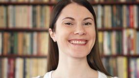 Estudiante universitario de sexo femenino que sonríe en biblioteca Primer día de escuela Estantes del estante para libros en fond metrajes
