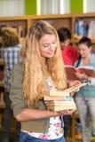 Estudiante universitario de sexo femenino que sostiene los libros en biblioteca Foto de archivo libre de regalías