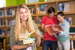 Estudiante universitario de sexo femenino que sostiene los libros en biblioteca Imagen de archivo libre de regalías