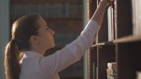 Estudiante universitario de sexo femenino que toma el libro del estante en biblioteca mano de la ventaja en los estantes con los  almacen de metraje de vídeo