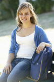Estudiante universitario de sexo femenino Sitting On Bench con el libro Imagen de archivo