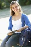 Estudiante universitario de sexo femenino Sitting On Bench con la mochila Imagenes de archivo