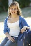Estudiante universitario de sexo femenino Sitting On Bench con la mochila Fotos de archivo libres de regalías