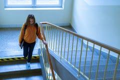 Estudiante universitario de sexo femenino solo deprimido joven que camina abajo de las escaleras en su escuela, mirando abajo Fotografía de archivo
