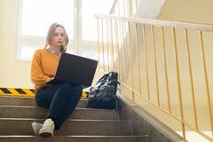 Estudiante universitario de sexo femenino solo deprimido joven que se sienta en las escaleras en su escuela, escribiendo en su or Fotografía de archivo libre de regalías