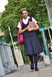 Estudiante universitario de sexo femenino Wearing Uniform Walking en la acera foto de archivo libre de regalías