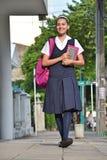 Estudiante universitario de sexo femenino Wearing Uniform Walking en la acera fotos de archivo