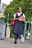Estudiante universitario de sexo femenino Wearing Uniform Walking en la acera foto de archivo