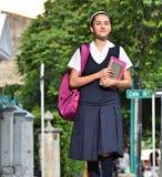 Estudiante universitario de sexo femenino Wearing Uniform Walking en la acera fotos de archivo libres de regalías
