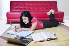 Estudiante universitario de sexo femenino Writing en los libros Fotografía de archivo libre de regalías