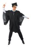 Estudiante universitario de sexo masculino asiático en el salto del vestido de la graduación Fotos de archivo